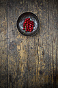 Bowl of red currants, Ribes rubrum, on dark wooden table, elevated view - LVF001614