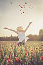 Woman jumping in a poppy field throwing petals in the air - SARF000736