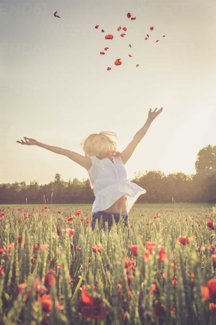 Woman jumping in a poppy field throwing petals in the air - SARF000736 - Sandra Rösch/Westend61