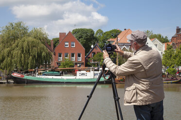 Germany, Lower Saxony, Leer, senior man taking a picture of the museum harbour with his camera - WIF000895