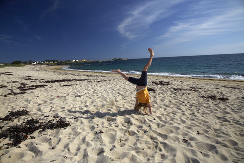 France, Bretagne, Finistere, Trevignon, Girl doing cartwheel on beach - DHL000471