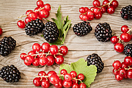 Red currants, blackberries and leaves on wooden table, elevated view - SARF000723