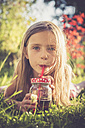 Portrait of little girl lying on a meadow in the garden drinking juice - SARF000728