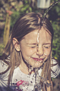 Little girl refreshing her face with a jet of water - SARF000731