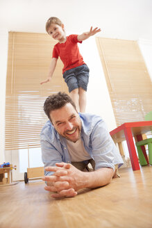 Son balancing on his fathers back in the nursery - MMFF000286