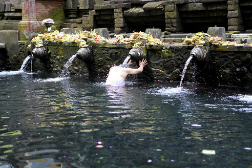 Indonesia, Bali, Pura Tirta Empul, man with head under water jet standing in a pool - FA000048