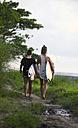 Indonesia, Bali, Canggu, two women with surfboards walking along footpath - FAF000050