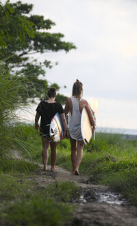 Indonesia, Bali, Canggu, two women with surfboards walking along footpath - FAF000050