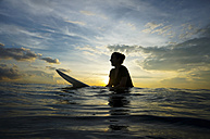 Indonesia, Bali, Canggu, silhouette of young woman with surfboard by twilight - FAF000052