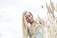 Portrait of smiling young woman standing in a rye field - DRF000952
