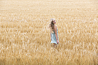 Portrait of smiling young woman standing in a rye field - DRF000954