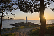 Spain, Galicia, Lighthouse at beach of Leis de Nemancos at sunset - LAF001061