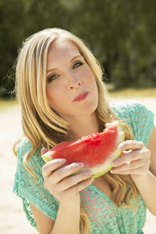 Portrait of young woman eating slice of watermelon - GDF000358
