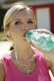 Portrait of young woman with earphones drinking water out of a bottle - GDF000359