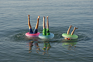 Italy, Adria, Children are diving in the sea with a floating tire - LBF000859