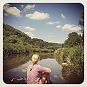 Belgium, Province Luxembourg, The Ardennes, woman/ hiker resting at Semois River, region Vresse-sur-Semois - GWF003033
