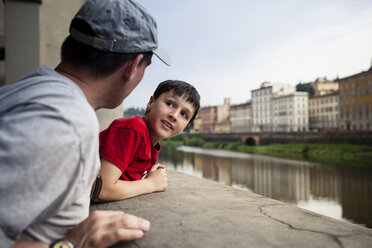 Italy, Tuscany, Florence, father and son leaning on balustrade in front of Arno River - SBDF001028