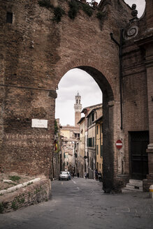Italy, Tuscany, Siena, city gate with tower of Palazzo Pubblico in the background - SBDF001038