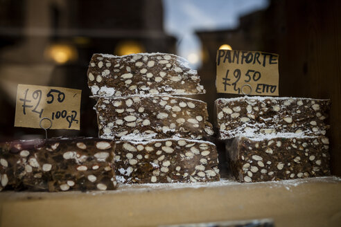 Italy, Tuscany, Pisa, shop window with traditional Tuscan fruit cake Panforte - SBDF001069