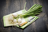 Bunch of spring onions and knife on clothes and dark wood - MAEF008843
