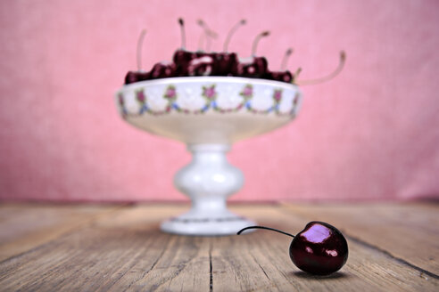 Etagere of cherries on wooden table with one cherry in the foreground - VTF000344