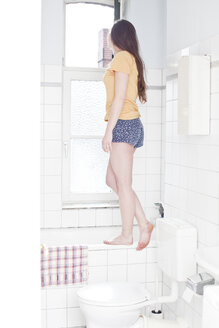 Young woman standing on rim of tub in the bathroom looking out of window - FEXF000172