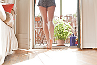 Young woman walking on her balcony - FEXF000173