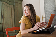 Portrait of smiling young woman with her laptop at home - FEXF000228