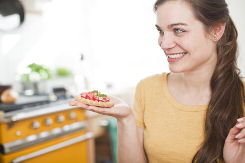 Young woman with strawberry tartelet on her hand - FEXF000180