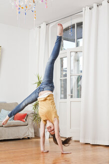 Young woman doing handstand in her living room - FEXF000195