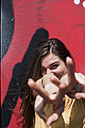 Portrait of smiling young woman showing victory-sign in front of a graffiti - FEXF000207