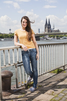 Germany, Cologne, portrait of smiling young woman standing in front of Rhine Rive - FEXF000213