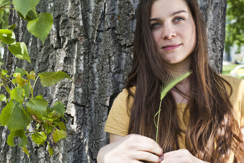 Portrait of young woman with spike in her hand sitting in front of tree trunk - FEXF000220