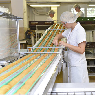 Germany, Saxony-Anhalt, woman controlling cookies on production line in a baking factory - LYF000277