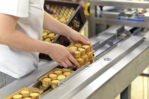 Germany, Saxony-Anhalt, woman taking pack of cookies from production line in a baking factory, partial view - LYF000248