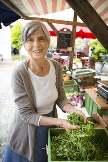 Portrait of smiling senior saleswoman with roquette at her vegetable stand - FX000036