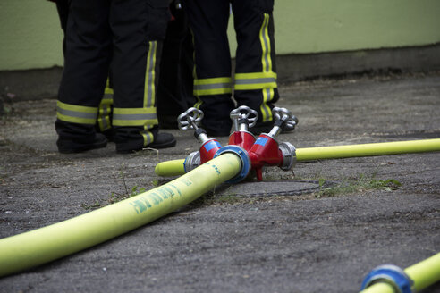 Germany, Bavaria, Firehose with valve, Firefighters in the background - YF000205