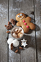 Gingerbread man, Christmas cookies and a mug of cocoa with cream on grey wood - CSF021991