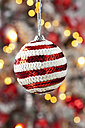 Christmas bauble decorated with red and white sequins hanging in front of blurred flares - CSF022030