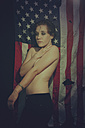 Shirtless young woman standing in front of American flag - VE000007