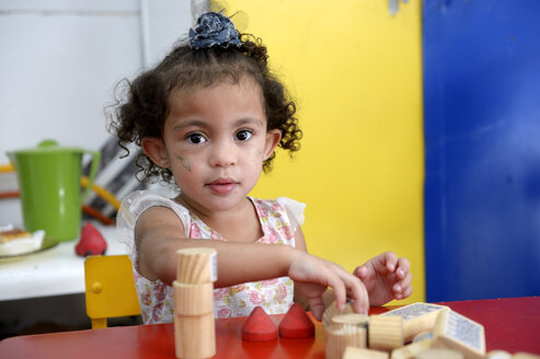 Brazil, Rio de Janeiro, Duque de Caxias, portrait of little girl playing with wooden building bricks in kindergarten - FLK000395