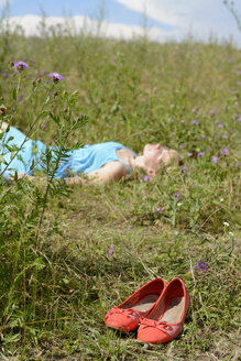Young woman lying in wildflower meadow - BFRF000479