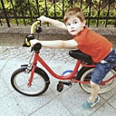 Little boy sitting on bicycle on pavement - ZMF000388
