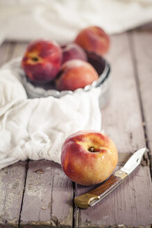 Bowl of peaches, knife and cloth on wood - SBDF001120