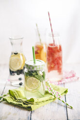 Carafes of miscellaneous fruit infused water on cloth and wood - SBDF001124