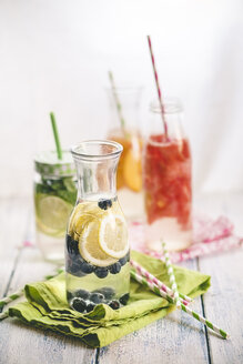 Carafes of miscellaneous fruit infused water on cloth and wood - SBDF001125