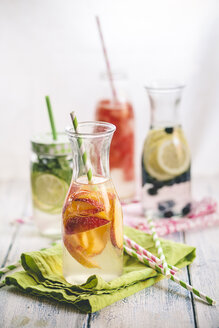 Carafes of miscellaneous fruit infused water on cloth and wood - SBDF001127