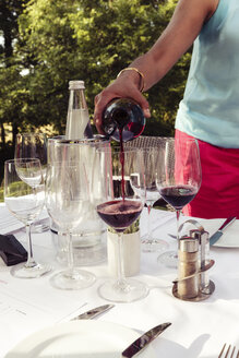 Woman pouring red wine into glass - EVGF000772