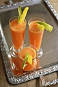 Three glasses of carrot mango orange smoothie on metal tray, elevated view - HAWF000412