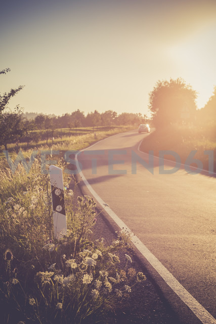 Driving car on country lane at evening twilight - LVF001699